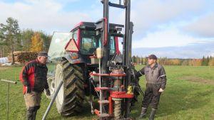 Kaksi miestä seisovat molemmin puolin traktoria, jonka taakse on kiinnitetty syvältä maasta näytteitä kairaava laitteisto.