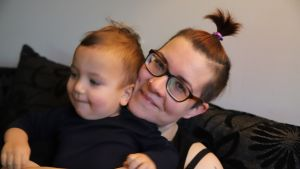 Äiti ja pieni lapsi istuvat sohvalla ja äiti hymyilee.