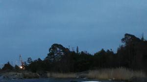 Moottorivene kallellaan meressä saaren edustalla.