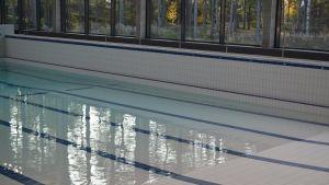 Iso uima-allas Kankaanpään uusitussa uimahallissa. Altaassa on uudet valkoiset pinnoitteet. Ikkunoista nälyy metsää.