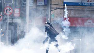 Mielenosoittaja heittää poliisin ampuman savukranaatin takaisin poliisia kohti.