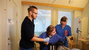 Fysioterapeutti Sami Backman ja sairaanhoitaja Siiri Lapinniemi auttavat potilasta Rovaniemen kuntoutussairaalassa.