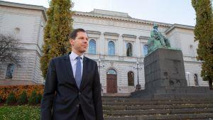 Johtokunnan neuvonantaja Mika Pösö seisoo Suomen Pankin pääkonttorin ulkoportaiden edessä. Taustalla näkyvä J. V. Snelmanin patsas on saanut kaulaansa siniseen nauhaan sidotun Abloy-avaimen.