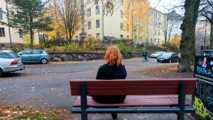 Nainen istuu penkillä Helsingissä.