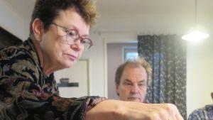 Nainen, Leena Ilmola kaataa kahvia vihreään kuppiin. Taustalla istuu mies, Seppo Kääriäinen.