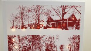 Valotaulu, missä punavalkoinen talomaisema, ja ledvalot loistavat kankaan takaa talojen ikkunoista.
