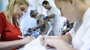 Vanhusta avustetaan sairaalassa Egerissä Unkarissa.