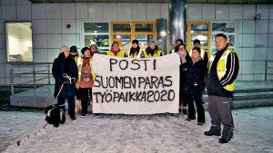 """Postin lakkoporukka on spreijannut valkoiseen lakanaan tekstin: """"Posti – Suomen paras työpaikka 2020"""""""