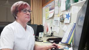 Sairaanhoitaja käyttää tietokonetta.