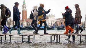 Ihmiset kulkevat tilapäisen penkeistä kootun sillan ylitse Venetsiassa 12. marraskuuta.