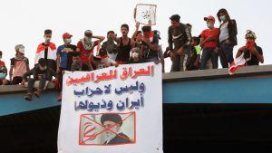 Irakilaisia mielenosoittajia roikottavat banneria sillalta jossa on Iranin Khamenein kuva.