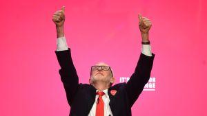 Kuvassa Jeremy Corbyn molemmat kädet ylhäällä ja katse ylöspäin suunnattuna.