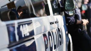 poliisi nojaa poliisiautoon