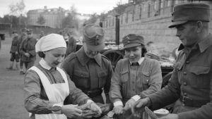 Lotat muonittavat ylimääräisiin kertausharjoituksiin lähteviä reserviläisiä Tampereen lyseon lukion pihassa 18.10.1939.