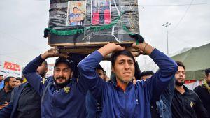Irakilaiset miehet kantavat arkkua Najafissa Irakissa.