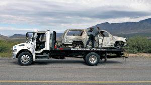 Pohjois-Meksikossa surmattiin yhdeksän yhdysvaltalaismormonia marraskuun alussa. Mies sitoo palanutta autoa kuljetuslavetille.