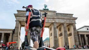 Mies siirtää sähköpotkulautoja Berliinissä.