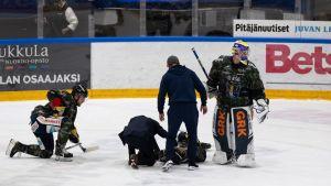 Jukurien Patrik Puistolaa hoidettiin jään pinnassa tiistaina, kun hän loukkaantui Ilveksen Panu Miehon taklauksen seurauksena.