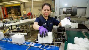 Työntekijä siirtelee käsin kuuden pöytäkynttilän pakkauksia hihnalta toiselle.