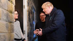 Britannian pääministeri Boris Johnson kotiinkuljettaa maitoa Debbie  Monaghanille Guiseleyssä, Leedsissä 11. joulukuuta