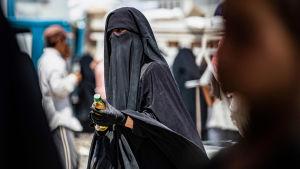 Niqabiin pukeutunut nainen sai ruoka-apua al-Holin leirillä Syyriassa 22. heinäkuuta.