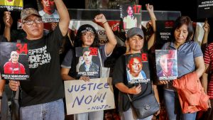 Mielenosoittajilla on joukkomurhan uhrien kuvia kylteissään.