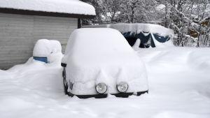 Auto hautautuneena lumeen.