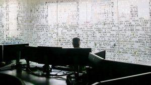 Työntekijä huoneessa tietokoneen ääressä.