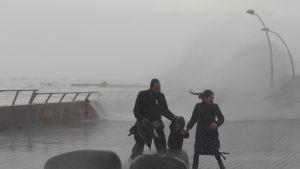 Perhe juoksee karkuun suuria tyrskyjä Tel Avivin rannassa Israelissa.