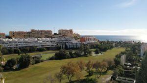 Golfkenttä, taustalla rakennuksia ja meri.