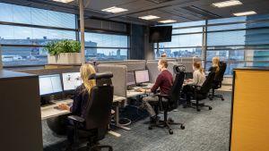 Danske Bankin chat-palvelua hoidetaan valoisassa avokonttorissa Helsingin Pasilassa.  Töitä tehdään näyttöpäätteiden ääressä. Työvuorossa on kolme nuorta naista ja yksi mies.