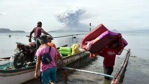 Ihmisiä ja purkautuva tulivuori taustalla.