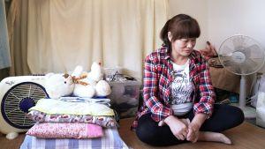 Kiinalainen ompelija Guo Yuqin istuu lattialla. Hashima, Japani.