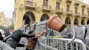 Mielenosoittaja heittää suurikokoisen kukkaruukun kohti mellakkapoliiseja Beirutissa.