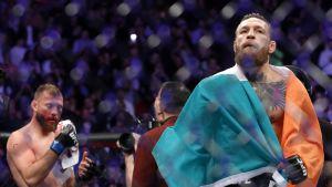 Conor McGregor juhlii voittoa, Donald Cerrone pyyhkii taustalla verta kasvoiltaan.