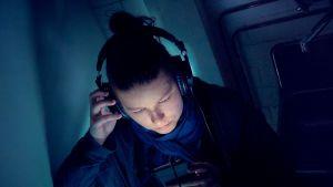 Nainen katsoo puhelinta kuulokkeet korvillaan.