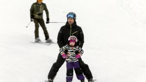 Mies ja lapsi laskettelevat.