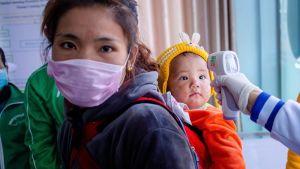 Kiinaan matkustavat tutkitaan nyt tarkkaan. Tässä terveysviranomaiset syynäävät lapsen ruumiin lämpötilaa Myanmarin ja Kiinan rajalla.
