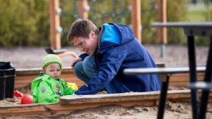 Isä ja lapsi leikkipuistossa.