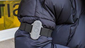 Siniseen toppatakkiin pukeutuneen henkilön käsivarren ympärillä on mustaan noin kahden senttimetrinlevyiseen kuminauhaan kiinnitetty harmaa urheilukellonkokoinen kappale, joka on ilmanlaatumittari OO.