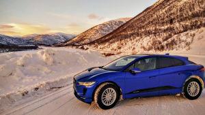 Sähkökäyttöinen, sininen Jaguar tuntureiden keskellä.