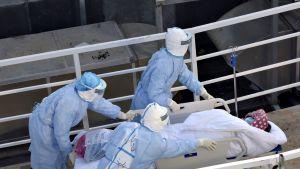 Koronaviruspotilasta siirretään sairaalan sisään Kiinan Wuhanissa 4. helmikuuta 2020.