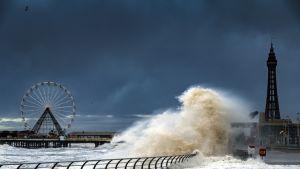 Kuvassa korkea myrskyaalto Britannian Blackpoolissa. Kuvassa taustalla vasemmassa laidassa on maailmanpyörä.