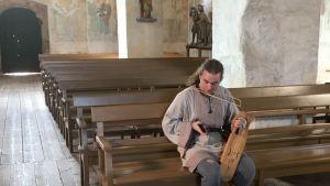 Vilppu Vuori jouhikko kädessään, kuvattu Hattulan Pyhän Ristin kirkossa.