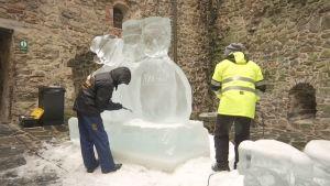 2 miestä veistää jäätä.