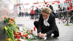 Nainen sytyttää kynttilän Hanaun iskun uhrien muistoksi.