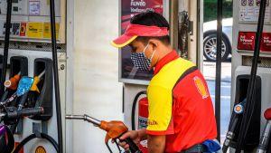 Työntekijä hengityssuojain kasvoillaan tankkaa asiakkaan autoa bensa-asemalla Bangkokissa 9. maaliskuuta.