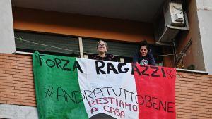 Kuvassa italialaiset oleskelevat maan lipulla koristetulla parvekkeella.