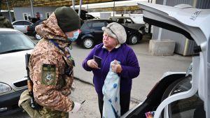 Ukrainalainen rajavartija tarkistaa rajalla naista.