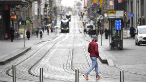Jalankulkijoita hiljaisella Aleksanterinkadulla Helsingissä keskiviikkona 18. maaliskuuta